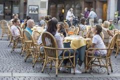 Os povos sentam-se em tabelas pequenas no café da rua fotografia de stock royalty free