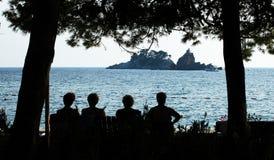 Os povos sentam-se em um banco e relaxam-se na praia sob as árvores em Montenegro Paisagem do recurso Foto de Stock