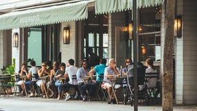 Os povos sentam-se fora do café próximo imagem de stock royalty free