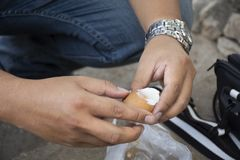 Os povos tailandeses do homem que descascam ovos cozidos do escudo onsen na mola quente do Pa Tueng em Mae Chan em Chiang Rai, Ta imagens de stock