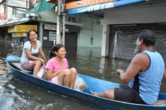 Os povos tailandeses mantêm-se sorrir e rir em uma rua inundada de Banguecoque, Tailândia, no 6 de novembro de 2011 fotos de stock