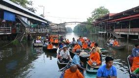 Os povos tailandeses rezam e põem o alimento e as ofertas da coisa à procissão das monges no barco video estoque