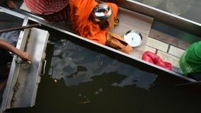 Os povos tailandeses rezam e põem o alimento e as ofertas da coisa à procissão das monges no barco filme