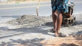 Os povos tailandeses usam compressores do solo no funcionamento do canteiro de obras e reparam a superfície da estrada em estrada video estoque