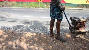 Os povos tailandeses usam compressores do solo no funcionamento do canteiro de obras e reparam a superfície da estrada em estrada vídeos de arquivo