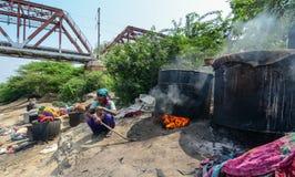 Os povos tingem a roupa tradicional no riverbank imagem de stock