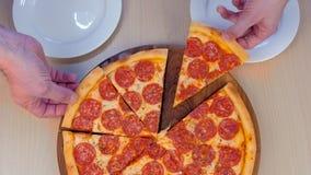 Os povos tomam fatias de pizza em suas placas, opinião superior do salame do close-up video estoque