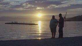 Os povos tomam imagens no fundo do por do sol sobre o Oceano Pacífico vídeos de arquivo