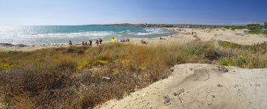 Os povos tomam o banho do sol na praia situada perto da cidade de Sampieri, Sicília imagens de stock royalty free