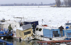 Os povos tomam o barco para fora prendido do Danube River congelado Fotos de Stock