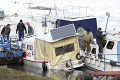 Os povos tomam o barco para fora prendido do Danube River congelado Imagens de Stock