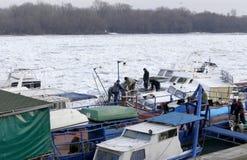 Os povos tomam o barco para fora prendido do Danube River congelado Imagem de Stock
