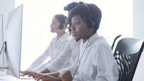 Os povos trabalham no centro do contato Mulher no funcionamento dos auriculares vídeos de arquivo