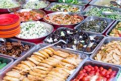Os pratos asiáticos diferentes venderam em um restaurante asiático exterior em sejam Fotos de Stock
