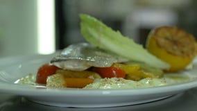 Os pratos de serviço pescam e os vegetais polvilham com o limão do queijo no restaurante vídeos de arquivo