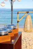 Os pratos inoxidáveis para o bufete na areia encalham Imagem de Stock