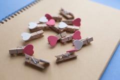 Os pregadores de roupa com corações são bloco de notas Papel azul do fundo Foto de Stock