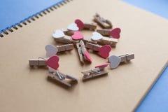 Os pregadores de roupa com corações são bloco de notas Papel azul do fundo Foto de Stock Royalty Free