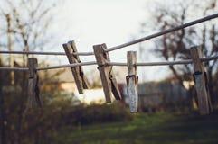 Os pregadores de roupa de madeira velhos penduram na corda Efeito que tonifica Instagram foto de stock