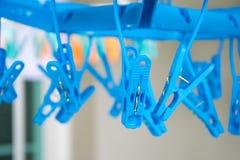Os pregadores de roupa plásticos azuis que penduram com suspensão cavilham no fundo Fotografia de Stock Royalty Free