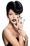 Os pregos, os bordos e os olhos da mulher do encanto pintaram o preto da cor. fotos de stock