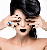 Os pregos, os bordos e os olhos da mulher do encanto pintaram o preto da cor Foto de Stock