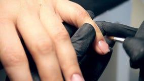 Os pregos profissionais importam-se no processo, esteticista nas luvas pretas que fazem a pregos o cliente fêmea para um tratamen video estoque