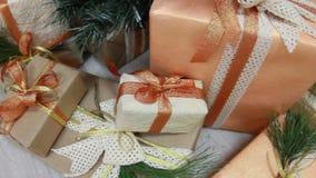 Os presentes apresentam caixas sob a árvore de abeto decorada do Natal com os brinquedos e a luz branca que pisc a festão Deslize vídeos de arquivo