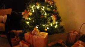 Os presentes apresentam caixas sob a árvore de abeto decorada do Natal com os brinquedos e a luz branca que pisc a festão Deslize filme