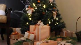 Os presentes apresentam caixas sob a árvore de abeto decorada do Natal com os brinquedos e a luz branca que pisc a festão Deslize video estoque