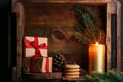Os presentes de Natal com cookies e vela iluminam-se no fundo de madeira Fotografia de Stock