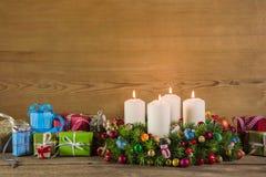 Os presentes de Natal e o advento envolvem-se no backgrou colorido de madeira Fotos de Stock