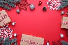 Os presentes do Natal apresentam com decorações em um fundo vermelho fotos de stock royalty free