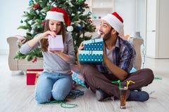 Os presentes do Natal da abertura da amiga e do noivo Fotos de Stock Royalty Free