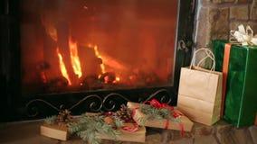 Os presentes do Natal decorados com ramos do abeto vermelho, cones, fitas colocam pela chaminé Queimadura morna do fogo de log Na filme