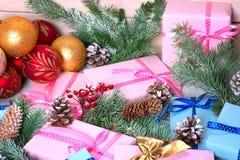 Os presentes do Natal e o abeto coberto de neve ramificam com os cones Foto de Stock Royalty Free