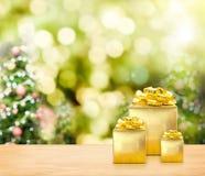 Os presentes dourados no tampo da mesa de madeira com árvore de Natal borraram a BO Imagens de Stock