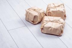 Os presentes embalados no pacote do papel do ofício amarraram uma corda em um carvalho branco d Fotos de Stock Royalty Free
