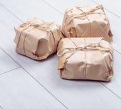 Os presentes embalados no pacote do papel do ofício amarraram uma corda em um carvalho branco d Foto de Stock