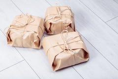 Os presentes embalados no pacote do papel do ofício amarraram uma corda em um carvalho branco d Imagem de Stock Royalty Free