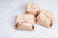 Os presentes embalados no pacote do papel do ofício amarraram uma corda em um carvalho branco d Fotografia de Stock Royalty Free