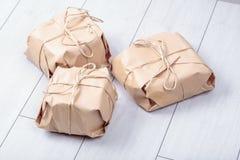 Os presentes embalados no pacote do papel do ofício amarraram uma corda em um carvalho branco d Imagens de Stock Royalty Free