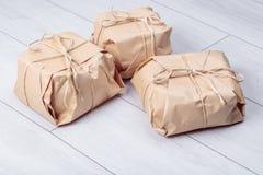 Os presentes embalados no pacote do papel do ofício amarraram uma corda em um carvalho branco d Imagens de Stock