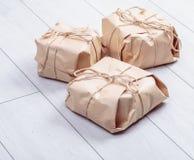 Os presentes embalados no pacote do papel do ofício amarraram uma corda em um carvalho branco d Imagem de Stock