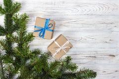 Os presentes envolvidos do Natal na tabela de madeira rústica escura com cones e abeto do pinho ramificam Com espaço da cópia par Fotos de Stock