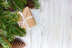 Os presentes envolvidos do Natal na tabela de madeira rústica escura com cones e abeto do pinho ramificam Com espaço da cópia par Fotos de Stock Royalty Free
