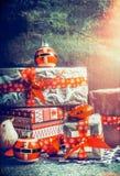 Os presentes festivos e os presentes do Natal que decoram com corte feito a mão forram flocos de neve e fitas vermelhas no fundo  Imagens de Stock