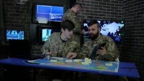 Os pro soldados no uniforme, veem a tabuleta digital e o trabalho no portátil, na instrução, na base militar, discutindo o assalt video estoque