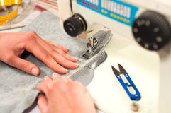 Os processos de costura na máquina de costura costuram a máquina de costura das mãos das mulheres Foto de Stock Royalty Free