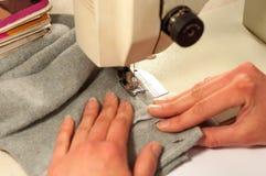 Os processos de costura na máquina de costura costuram a máquina de costura das mãos das mulheres Imagens de Stock